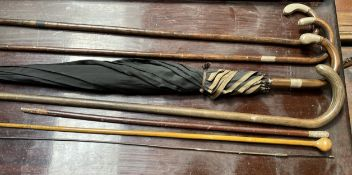 Two silver topped and bamboo walking sticks, together with another walking stick, parasol,