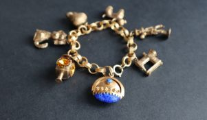 A 9ct gold charm bracelet set with numerous charms including a sewing machine, a poodle, acorn,