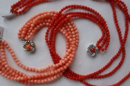 A three strand coral bead necklace to a white metal clasp,