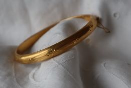 An 18ct gold hinged bracelet with star decoration,