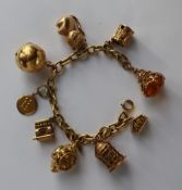 An 18ct yellow gold oval link bracelet, set with numerous 9ct yellow gold charms including a castle,