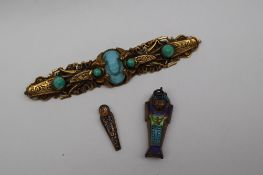 An Egyptian yellow metal bar brooch set with hardstones together with a Tutankhamun enamel