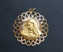 An 18ct yellow gold pendant of pierced circular form, with a head in profile, 47mm diameter,
