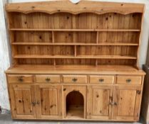A large pine dresser, with a shaped cornice above two shelves, the base with five drawers,
