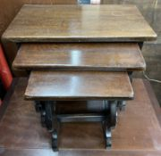 An oak nest of three tables with rectangular tops and shaped supports