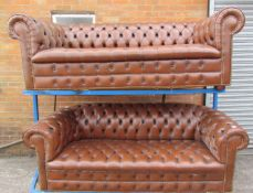 A pair of brown leather chesterfield three seater settees on bun feet
