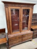 A 19th century mahogany bookcase, with a moulded cornice above a pair of glazed doors,