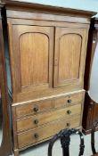 A Victorian oak linen press, the moulded cornice above a pair of cupboard doors enclosing shelves,