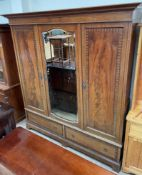 An Edwardian mahogany triple wardrobe, the moulded cornice above a central mirrored door,
