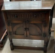 A 20th century oak side cabinet with a frieze drawer and a pair of oak doors