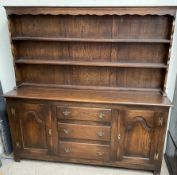 A 20th century oak dresser the rack with two shelves and a planked back,