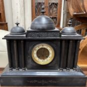 A black slate mantle clock with three domes above an architectural front and plinth base,
