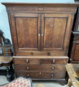 A 19th century oak linen press, with a moulded cornice above a pair of cupboard doors,