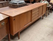 A mid 20th century teak sideboard with a bank of four drawers to the centre and cupboards with