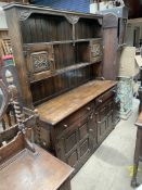 A 20th century oak dresser, the rack with carved door and shelves,