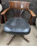 A 20th century upholstered captains chair with a pierced splat on a rotating base
