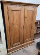 A pine linen cupboard, with shelves to one side and hanging space to the other,