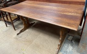 A 20th century oak refectory table with a rectangular top on pierced ends,