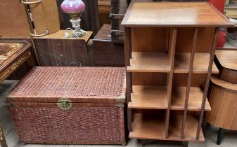 A teak revolving bookcase, with a square top above three shelves on a rotating base,