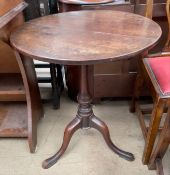A 19th century mahogany tripod table with a circular top on a baluster column and three legs