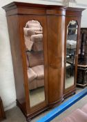 An Edwardian mahogany wardrobe, the moulded cornice above two mirrored doors on ball feet,