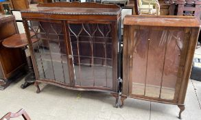 A 20th century mahogany display cabinet with a serpentine front,