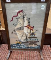 A 20th century oak framed fire screen with a woolwork of a ship
