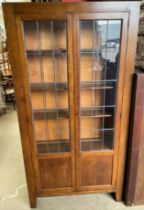 A 20th century oak bookcase with a pair of leaded glass doors on stiles,
