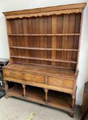 An 18th century South Wales oak dresser, the moulded cornice above three shelves,
