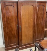 A Victorian mahogany triple wardrobe, with a moulded cornice above three doors on a plinth,