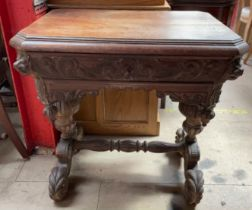 A 19th century Low Countries carved oak side table, carved with lions on scrolling feet,