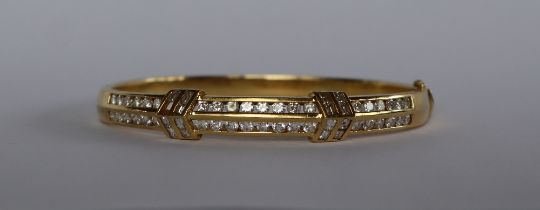 An 18ct yellow gold diamond set hinged bangle, set with two rows of brilliant cut diamonds,