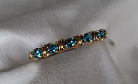 A 14ct yellow gold blue topaz and diamond set hinged bangle,