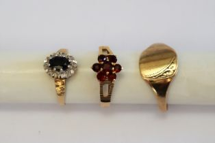 A 9ct gold signet ring together with a 9ct gold garnet set ring and a gem set 9ct gold ring
