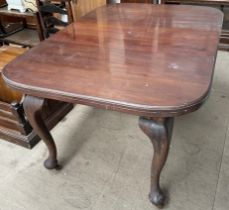 A mahogany extending dining table on cabriole legs and pad feet and casters