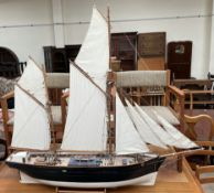 A model ship, with two masts and sails unfurled, on a stand,