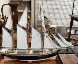 A model ship, with three masts and unfurled sails, bears a plaque for Jane Banks, Bideford,
