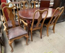 A reproduction mahogany extending dining table with an additional leaf together with a set of six