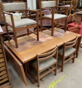 A mid 20th century Danish teak tiled top extending dining table and eight chairs,