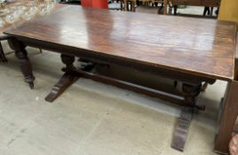 An oak refectory table of rectangular form with a carved frieze on cup and cover legs