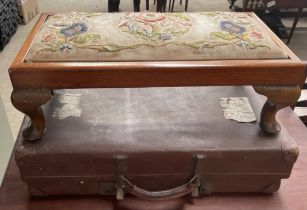 A footstool with embroidered top on cabriole legs together with a suitcase