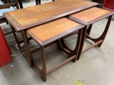 A mid 20th century teak nest of tables, with a crossbanded coffee table and two occasional tables,