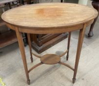 An Edwardian mahogany occasional table with an oval top on square tapering legs and spade feet