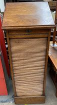 An oak tambour fronted filing cabinet, with a hinged, sloping top above a tambour front,