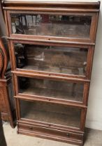 An oak four section bookcase with glazed doors, the base with a drawer on a plinth, 86.