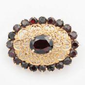 Granat - Brosche GG 750, ovale, floral durchbrochene Form, leicht gewölbt, Mitte bese