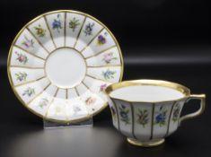 Tasse und Untertasse mit unterschiedlichen Blumen
