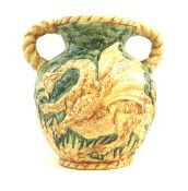 An unusual West German pottery double handled vase, decorated in relief with a dragon on a green