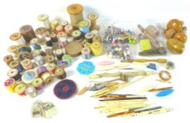 A collection of sewing and needlework items, including several bobbins, crocheting tools, reels of