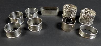 A collection of Edwardian and later silver napkin rings, including three Edwardian rings, two with